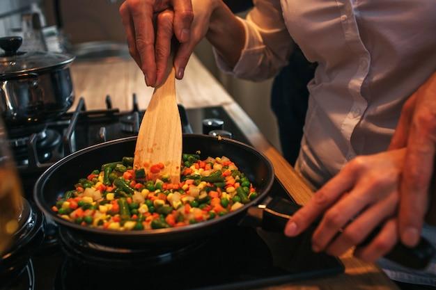 여자의 손을 잡고 남자의보기를 잘라. 그들은 함께 저녁을 요리합니다. 팬에 음식을 튀김 커플. 프리미엄 사진