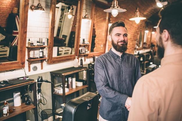 Вырезать вид человек в розовой рубашке пожимает руку парикмахера-стилиста. ему нравится работа, которую он сделал.