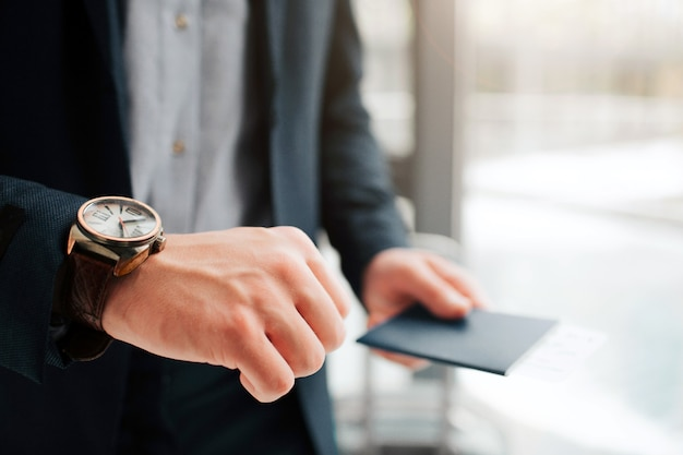 Вырезать вид человека в костюме стоит у окна. он показывает часы на левой руке. паспорт с билетом внутри находится в правом