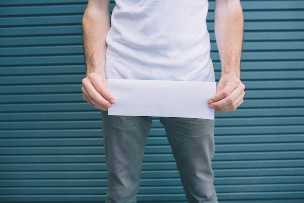 서서 그의 바지 위에 빈 페이지를 들고 남자의보기를 잘라. 남자는 소변에 문제가 있습니다. 줄무늬에 절연