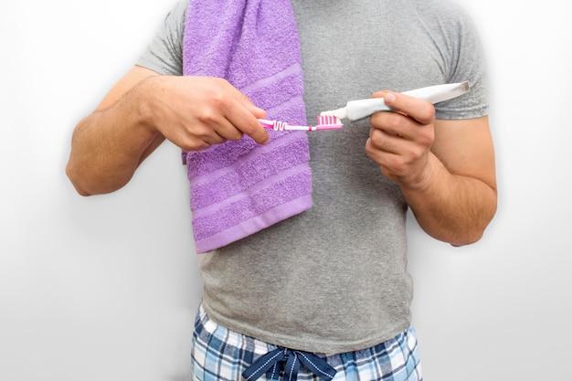 立って歯ブラシに歯磨き粉を置く男のビューをカットします。彼は肩に紫のタオルを持っています。彼はパジャマ姿で立っています。白で隔離されます。