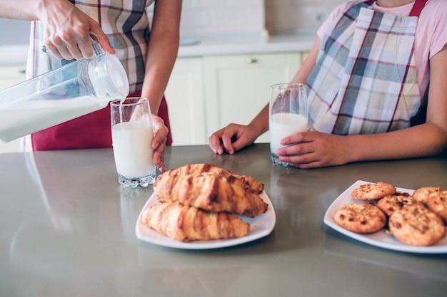 컵에 우유를 붓는 어머니의 손의보기를 잘라. 그녀는 한 손으로 잡고 있습니다. 소녀도 같은 일을하고 있습니다. 테이블에는 다양한 유형의 롤이 있습니다.