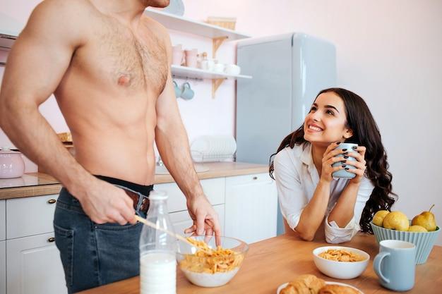Вырезать вид сексуальное мужское тело на кухне. парень встает за стол и смешивает молоко с кукурузными хлопьями. веселая молодая женщина смотрит на него и улыбается. она держит чашку.