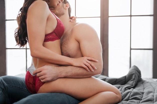 방에있는 침대에 남자의 다리에 앉아있는 빨간 란제리의 섹시한 젊은 여성의 컷보기