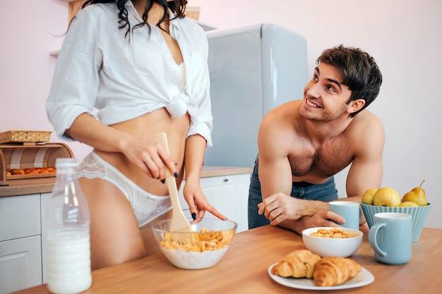 Отрежьте взгляд сексуальной стойки молодой женщины в кухне на таблице. она смешала кукурузные хлопья с молоком в миске. возбужденный молодой человек смотрит на нее и улыбается. он держит чашку.