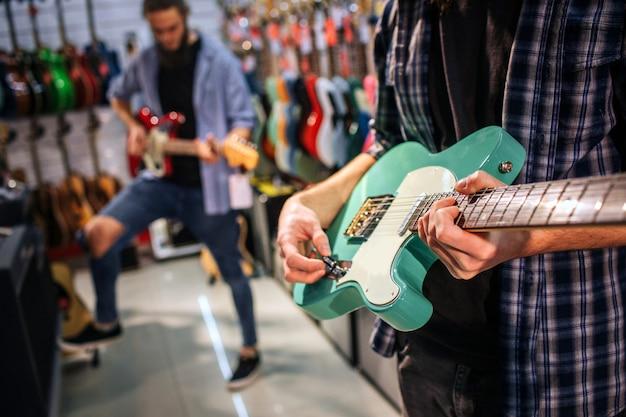 Отрежьте взгляд 2 молодых людей играя на электрических гитарах. сначала держите зеленый. второй парень держит коричневую гитару и имеет одну ногу выше другой.