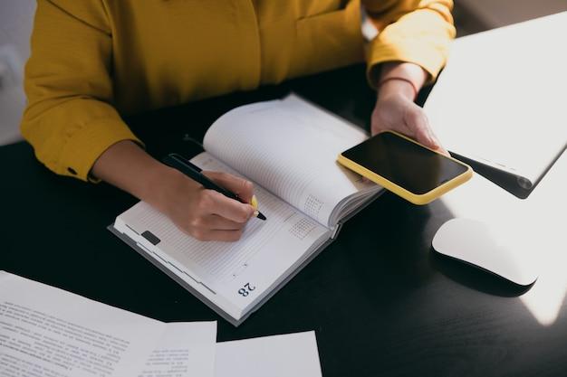 女性の手のカットビュー。日記やプランナーで書いていると電話を見ている黄色いブラウスの白人女性。上面図。黒い机の上の書類。手持ちの赤いブレスレット。在宅勤務。