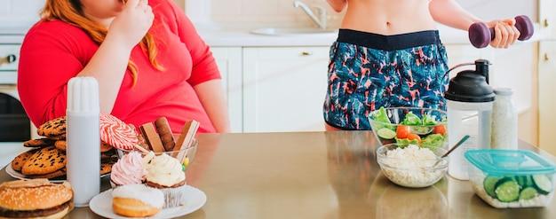 キッチンで若いスリムなモデルと太りすぎの女性のカットビュー。よくできた女の子は手にダンベルを持っています。太った女性は彼女を見て