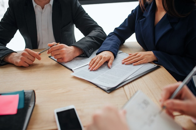 Cut view of people working together at one table in room. one person write in notebook. anoter point in book. guy hold pen.