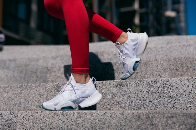 Cut view of slim fit woman legs in red leggins and white sneakers on blur background. female runner running on concrete stairs in city. closeup on shoes.