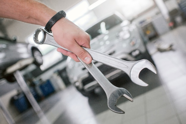 Cut view of strong man's hand holding two wrenches in front of white car. grey vehicle is on platform. there is clock on wrist.