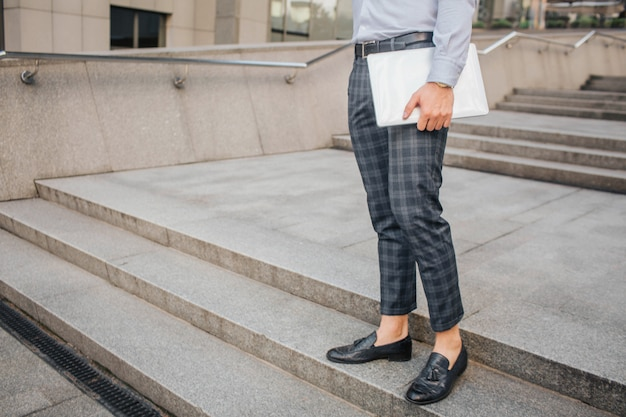 Cut view of stylish man stand and pose. he holds laptop with hand. young man stands on steps.