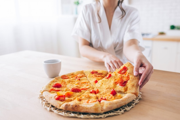 Cut view of woman in white dressing gown in kitchen. taking piece of pizza. small slice. young housekeeper live carefree life.