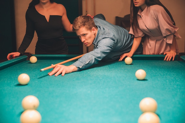 Cut view of young man looking concentrated. he aiming into billiard ball. two slim models stand behind him.