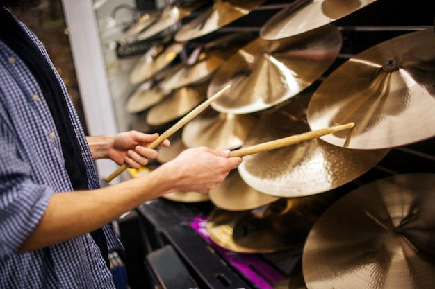 Cut view of young mantouching cymbals wit drum sticks. he stands alone in room.