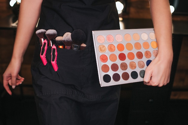 컷 보기 젊은 여성은 손으로 다채로운 아이섀도 팔레트를 들고 있습니다. 벨트 뒤의 브러쉬