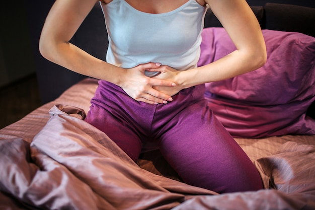 Cut view of young woman suffers from pain. she holds both hands on stomach. woman feels pain there. she is concentrated on that problem. woman sits on bed alone.