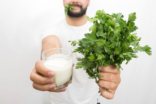 Cut vuew of bearded young man holding glass of kefir and bunch of parsley in hands. also young man has piece of parsley in mouth.