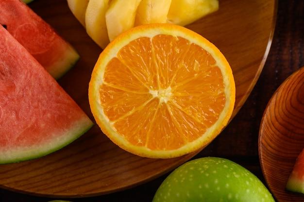 Вырезать арбузы, апельсины и ананасы на деревянной тарелке с яблоками.