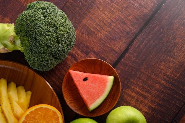 Вырезать арбузы, апельсины и ананасы с яблоками и брокколи на деревянной тарелке.