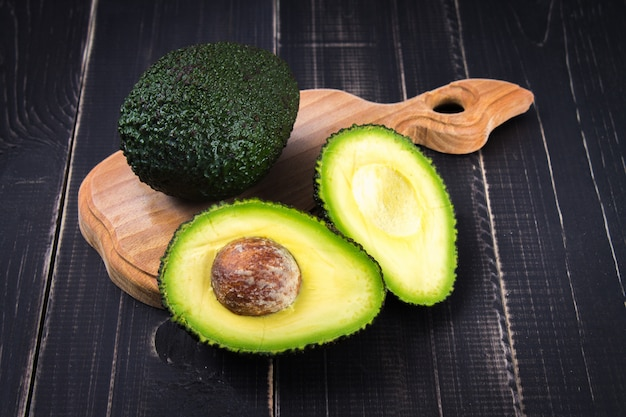 Cut and whole avocado on a wooden board on a black wooden background.