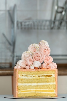 Бисквитный торт в разрезе. торт персикового цвета, украшенный зефиром.