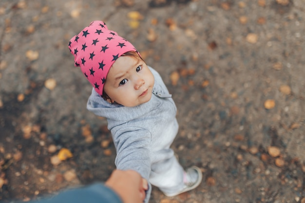 Cute 1 year old baby girl walking outdoors wearing in stylish overalls