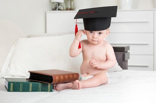 책과 함께 침대에 siting 및 졸업 모자를 벗고 귀여운 10 개월 된 아기