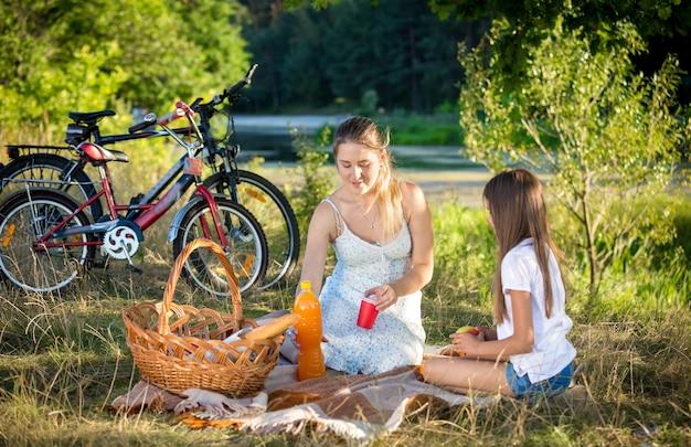젊은 어머니와 함께 강에서 피크닉 데 귀여운 10 살짜리 소녀