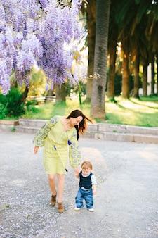 귀여운 18 개월 된 아기가 등나무 아래에서 어머니와 손을 잡고 걷고 있습니다.