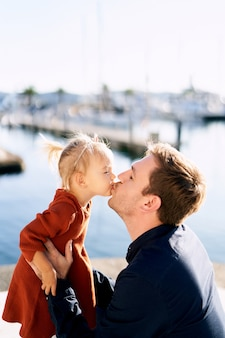 晴れた日に散歩しながらかわいい2歳のパパにキスをしています。