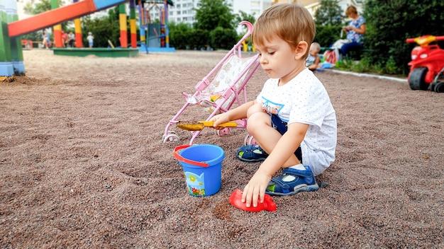 공원에서 어린이 놀이터에서 노는 귀여운 3 세 어린 소년. 삽으로 모래를 파는 유아