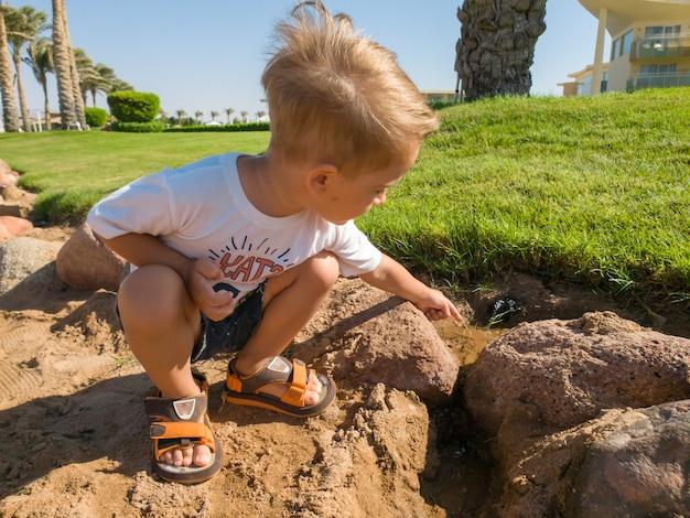 美しい芝生の芝生に座って、庭に水をまくために小さな小川に触れているかわいい3歳の男の子