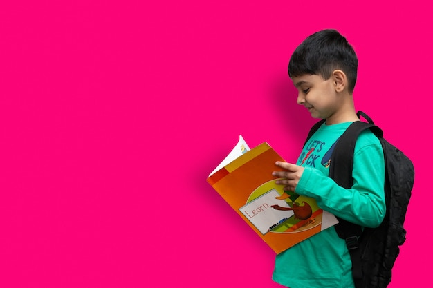 Симпатичный 7-летний счастливый мальчик со школьным рюкзаком, держащий книги на простом фоне для концепции образования