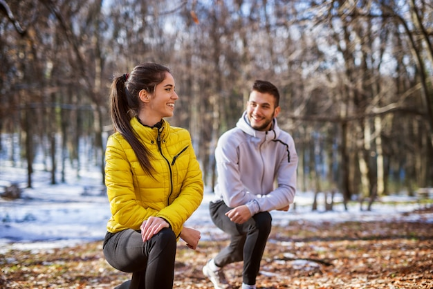 Cute active fitness girl in sportswear doing leg stretching with her personal trainer in the forest in the sunny winter morning.