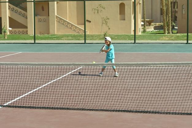 屋外でテニスをしているかわいいアクティブな女の子