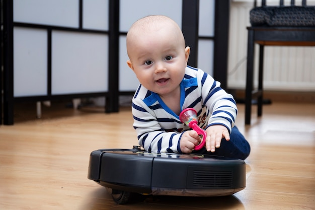 A cute adorable baby boy is riding on a robot vacuum cleaner at home with a baby rattle in one hand