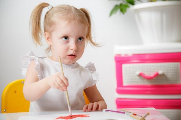 水の色で絵を学ぶかわいい愛らしい赤ちゃん女の子。カラフルなブラシを使用して、家庭で描く小さな幼児子供。色、自宅や保育園で水を試して健康的な幸せな娘