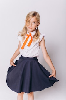 白い背景の上の制服でかわいい愛らしい白人ブロンディの女の子