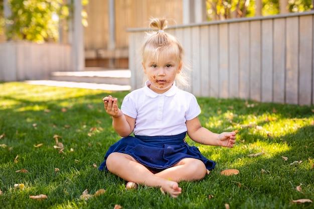 앉아서 먹는 딸기 과일 귀여운 사랑스러운 백인 유아 아기 소녀. 건강 한 간식을 먹고 공원에서 재미있는 아이. 아이들을위한 여름 맛있는 맛있는 손가락 음식.