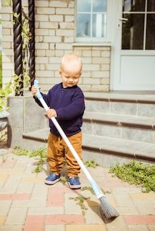 屋外の庭の裏庭でほうきを持って遊んでいるかわいい愛らしい白人の幼児の男の子