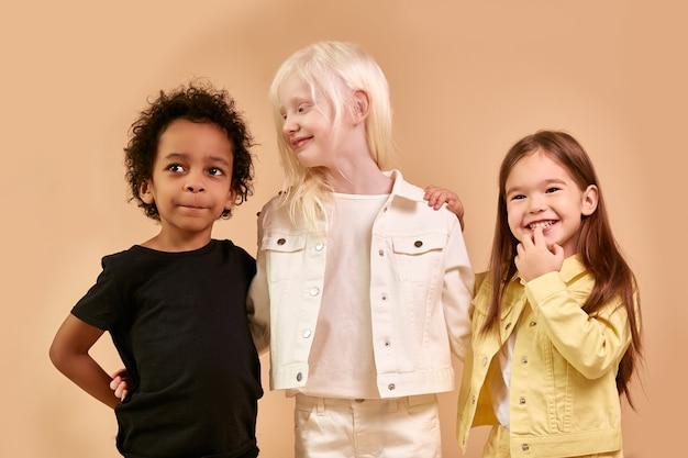 Симпатичные очаровательные разнообразные дети, улыбаясь вместе изолированные
