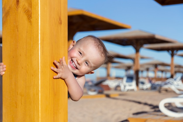 A cute adorable excited child is laughing and playing on the beach in hide and seek after swimming. baby boy is spending time with pleasure at the seaside of a tropical resort.