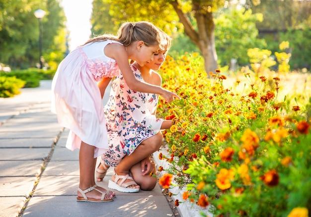 ピンクの繊細なドレスを着たかわいい愛らしい女の子は、明るい夏の公園で素晴らしい燃えるようなマリーゴールドを嗅ぎます