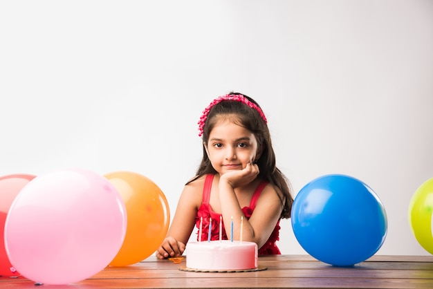 Cute adorable little indian or asian small girl celebrating birthday while holding strawberry cake and blowing candles at table or standing isolated over white or red background