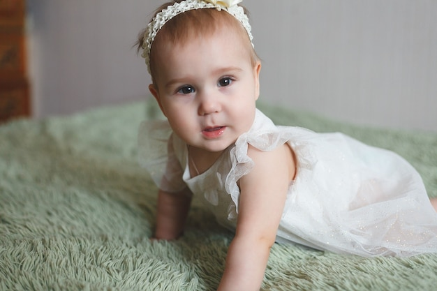 Cute adorable newborn baby of 3 moths with diapers. hapy tiny little girl or boy looking at the camera and white dress. dry and healthy body and skin for children concept. baby nursery