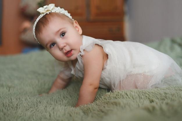 おむつをした 3 moのかわいい愛らしい新生児。カメラと白いドレスを見ている陽気な小さな女の子または男の子。乾燥した健康な体と肌を子どもたちのコンセプトに赤ちゃん保育園
