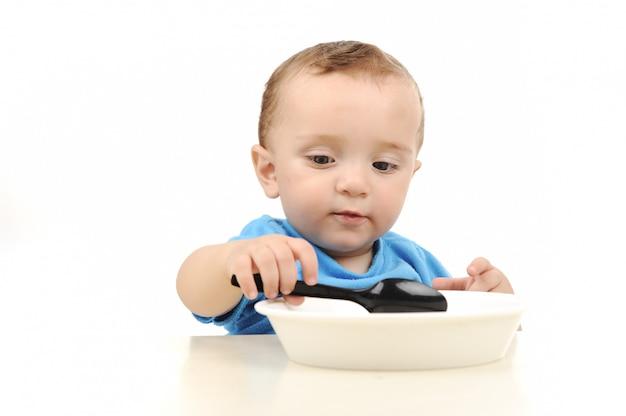 Симпатичный очаровательны один год ребенок с зелеными глазами, едят на столе, ложкой и пластины
