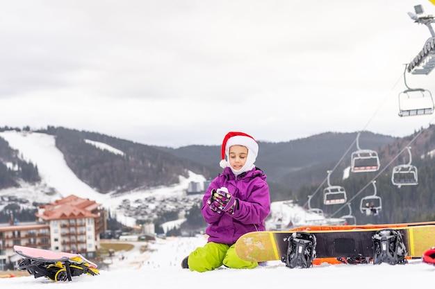 Cute adorable preschooler caucasian kid girl portrait little girl in santa hat and snowboard enjoy winter sport activities.