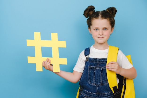Cute adorable schoolgirl with backpack holding big yellow hashtag symbol and happy looking at camera, showing hash sign, posing over blue background. concept of trendy social media posts and school
